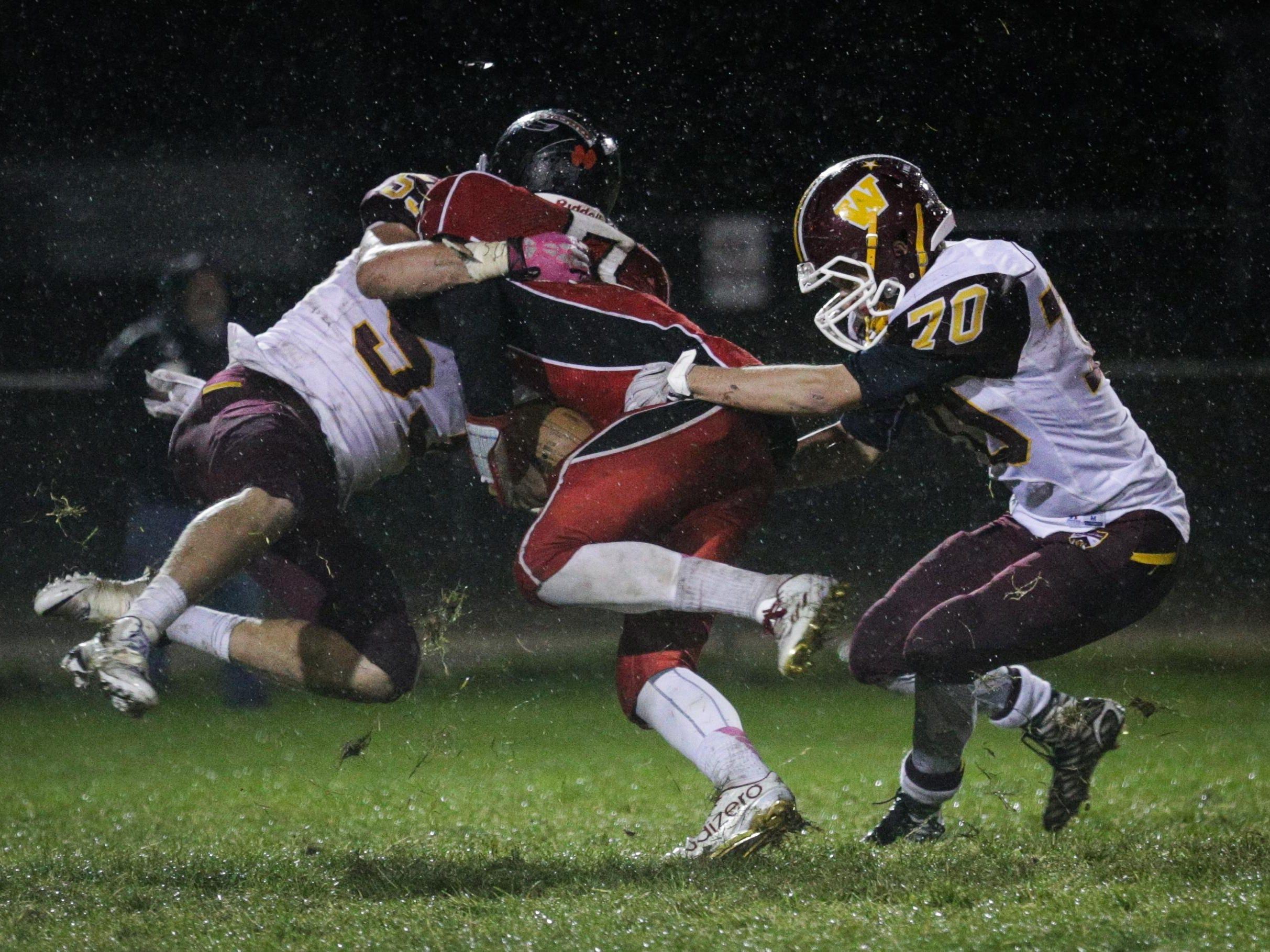 Windsor High School defenders Storm Fox, left, and Jesse Rhodes, sack Loveland High School quarterback Ayden Eberhardt during the third quarter in Loveland Colo. on Oct. 22, 2015.