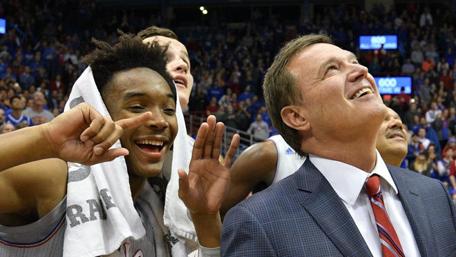 Devonte' Graham holds up six fingers while head coach Bill Self watches congratulatory messages from former players on his 600th win.