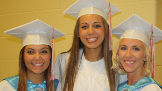 Dixie Heights High School seniors Devin Grover, Allison Neal and Sara Edgett smile for the camera just before their graduation ceremony in 2015.