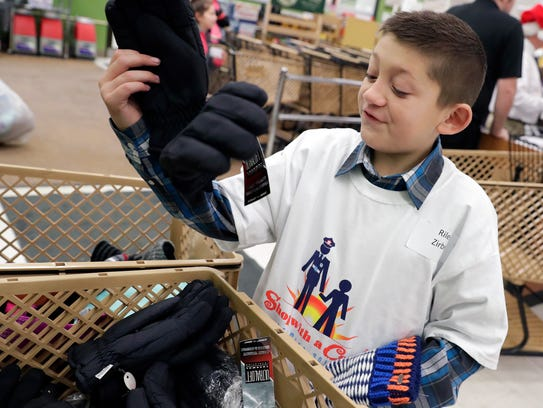 Riley Zirbel, 10, picks out a pair of gloves during the 23rd annual Shop with a Cop event held Saturday.