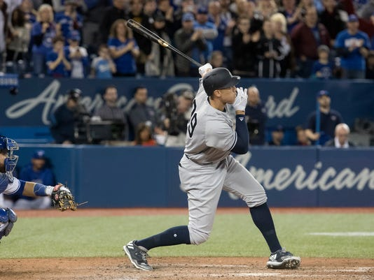 New York Yankees' Aaron Judge hits a single against the Toronto Blue Jays during the ninth inning of a baseball game in Toronto on Sunday, April 1, 2018. (Fred Thornhill/The Canadian Press via AP)