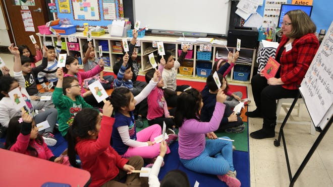 """Diane Gomez reads """"Corduroy"""" in Spanish to Mirjana Lezaja's first-grade class March 4 at Edison Elementary School in Port Chester, during the third annual World Read Aloud Day."""