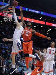 Virginia guard Kyle Guy (5) shoots in front of  Clemson guard Gabe DeVoe (10) during the second half of an NCAA college basketball game in the Atlantic Coast Conference men's tournament semfinals Friday, March 9, 2018, in New York. Virginia won 64-58. (AP Photo/Julie Jacobson)