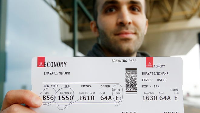 Iranian-born bioengineer researcher Nima Enayati holds up his boarding pass at the Milan's Malpensa International airport in Busto Arsizio, Italy, Sunday, Feb. 5, 2017. Just hours after an appeals court blocked an attempt to re-impose the travel ban, Iranian researcher Nima Enayati checked in on an Emirates Airline flight direct from Milan's Malpensa airport to New York's JFK on Sunday afternoon.