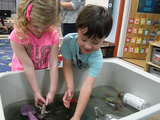 Reagan Hill and Landon Raub explore a water tank filled with garbage to show what can happen when people don't avoid littering. The tank was part of environmental awareness activities at The Goddard School.