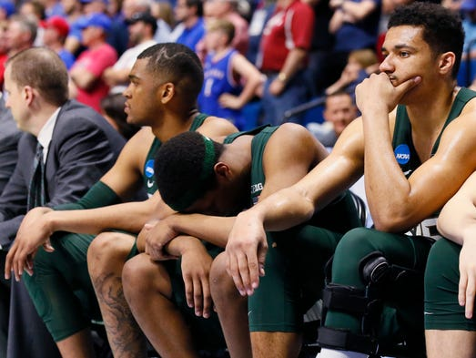 Michigan State players sit on the bench late in the