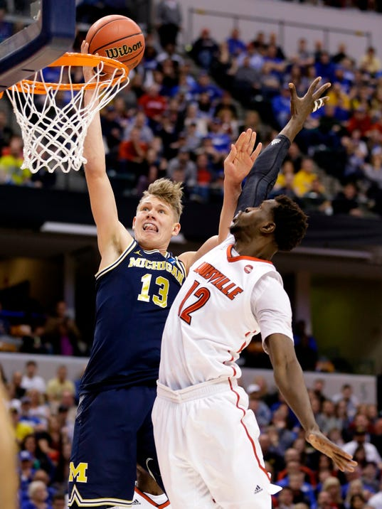 FILE - In this Sunday, March 19, 2017, file photo, Michigan forward Moe Wagner (13) shoots over Louisville forward Mangok Mathiang (12) during the second half of a second-round game in the men's NCAA college basketball tournament in Indianapolis.  Wagner has decided to sign with an agent and enter the NBA draft. The Michigan big man announced his plans Saturday, April 14, 2018 with an essay written for The Players' Tribune. (AP Photo/Michael Conroy, File)