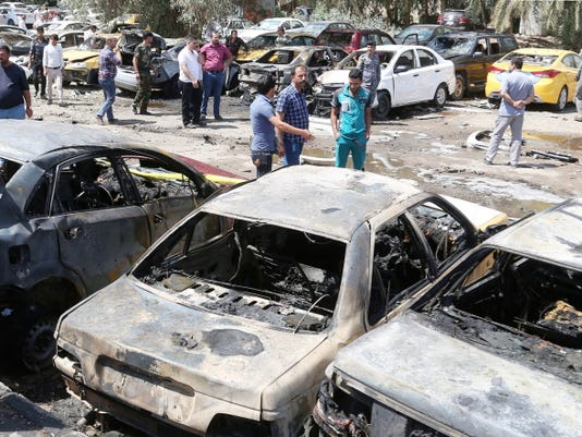 People and security forces gather at the scene of a car bomb explosion in a parking lot outside Yarmouk hospital in western Baghdad, Iraq, Tuesday, April 14, 2015. Car bombs went off Tuesday morning in and around the Iraqi capital, killing and wounding civilians, officials said.