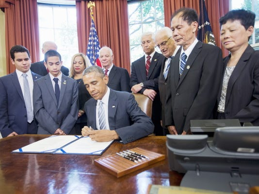 President Barack Obama signs S. 665, the Rafael Ramos and Wenjian Liu National Blue Alert Act of 2015, Tuesday, May 19, 2015, in the Oval Office of the White House in Washington. From left are, Justin Ramos, 19, Jayden Ramos, 14, Vice President Joe Biden, Maritza Ramos, Sen. Ben Cardin, D-Md., Rep. Dave Reichert, R-Wash., Rep. Bill Pascrell, D-N.J., Wei Tang Liu, and Xiu Li.