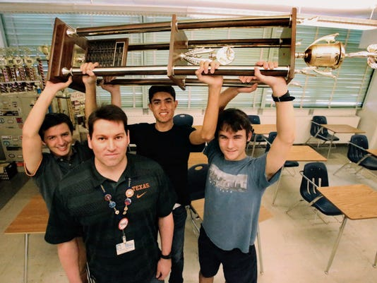 Rudy Gutierrez—El Paso Times Coronado students Luke Minton, left, Sheel Patel, center, and Andrew Paton hold the KCOS-TV High Q trophy they have won the past three years. Lead by their coach, Matthew Ballway, foreground, the team won a national trivia compeition this past weekend. Not pictured is team member Teddy Cai.