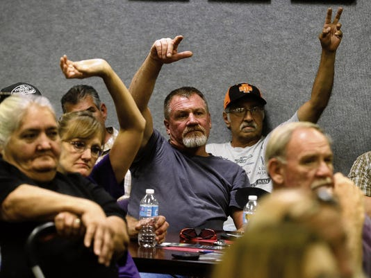 Aztec resident Guy Collier, center, waits his turn to speak Wednesday during a meeting at Aztec City Hall.