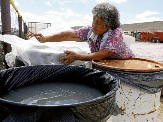 Shiprock resident Sarah Frank covers barrels of water provided by the Shiprock Chapter on Tuesday at her home in southeast Shiprock.