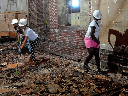 Crispus Attucks Charter School students Janiayah Williams, 17, left, Katelynn Torres, 19, and Ashley Demerzile, 17, right, help clean up the site of the future York County Food Bank in the 500 block of East King Street last week.