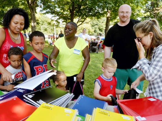 """From left, Marta Morales of York helps her children Hector Cora, 6; Yeidel Gonzales, 8; and Yedrieliz Cora, 3, choose school supplies with guidance from volunteer Latessa Jamison, while John Mears of Dillsburg watches as his son Jonathan, 4, receives a folder from volunteer MaKayla Long during a """"back to school bash"""" event hosted by Meeting Place Church at York's Lincoln Park on Saturday."""