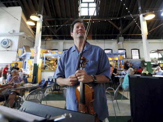 Lawrence Golan, the York Symphony Orchestra music director and conductor, acknowledges the applause of the people at Central Market after a performance on Saturday.
