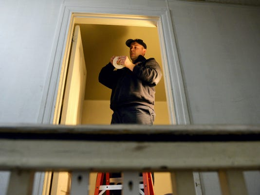 York City firefighter Clifton Frederick installs a smoke detector inside a second-story bedroom in a Manor Street home on Wednesday. He spent his last shift doing his normal duties.