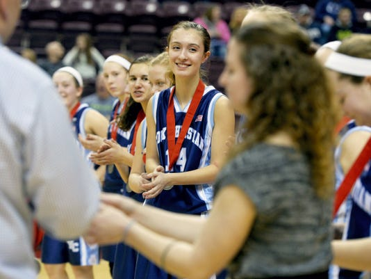 Christian School of York's Alex Landis applauds as her teammates receive their medals after losing the District 3 Class A championship game Thursday at Giant Center. Lebanon Catholic defeated Christian School of York, 40-20.
