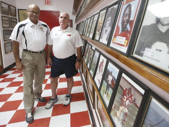 Mike Feely, Leon High School's athletic director, and Jimmy Sauls, who played integral roles with the Leon High School football team as the head coach, offensive and defensive coordinator from 1974-2000, stand in the school's trophy room on July 27, 2015.
