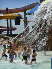 Children and adults hurry over to stand under the huge bucket dumping water on everyone in Buccaneer Bay at Castaway Cove Waterpark.