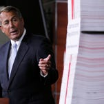 John Boehner with a tall stack of paper which represents the 20,000 pages of regulations of the Affordable Care Act regulations.