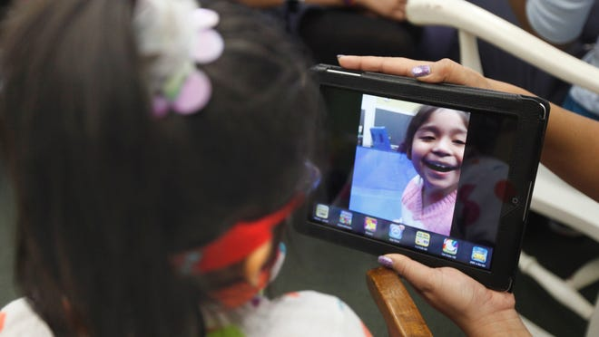 A student looks at a picture of herself on an iPad during a class for students with disabilities a few years ago at School 29 in Rochester. Proponents of the school technology bond act proposal think it will provide more such opportunities for students across the state.