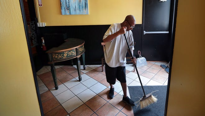 James Jackson tidies up the waiting area at a new Caribbean restaurant in Downtown Memphis. Following a childhood dream, Jackson's brother-in-law Arturo Azcarate is opening Curry N Jerk this week to honor his mother, a longtime chef at a California Marine base.
