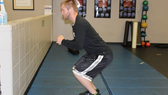Squat down as if sitting back in a chair.