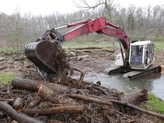 An excavator digs out a huge  a logjam on the Sac River,