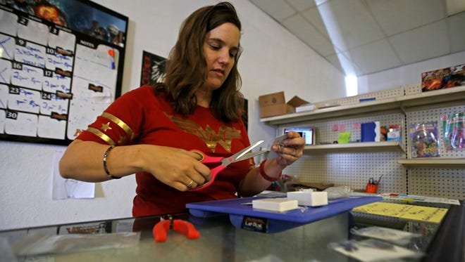 April Loughridge, owner of Ichigo Comics, packages handmade jewelry on Monday in the store at Hutton Plaza in Farmington.