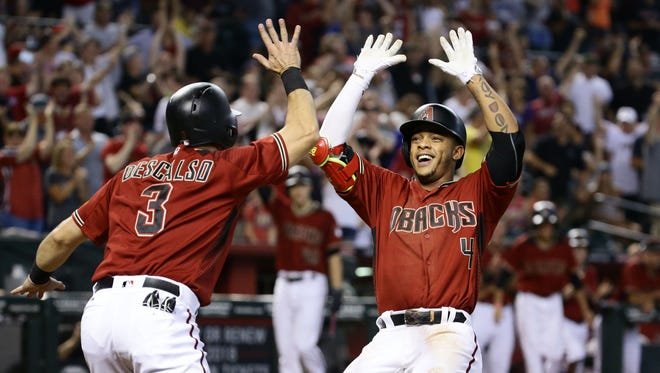 Arizona Diamondbacks' Ketel Marte (right) celebrates as he crosses home plate after hitting an inside-the-park home run with Daniel Descalso, who scored on the play, against the Atlanta Braves in the 4th inning on Wednesday, Jul. 26, 2017 at Chase Field in Phoenix, Ariz.