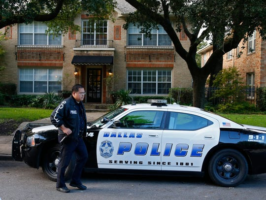 Dallas Police stand watch outside the apartment where