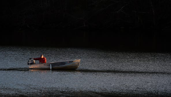 Larry Powell checks his depth finder as the sun sets