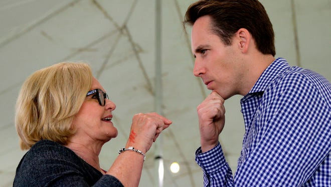 FILE - In this Aug. 17, 2017, file photo, Democratic U.S. Sen. Claire McCaskill, left, talks with Republican Missouri Attorney General Josh Hawley in Sedalia, Mo. Missouri Democrats are using Republican Gov. Eric Greitens' political and legal woes to try to attack Hawley, the top GOP candidate in a hotly contested U.S. Senate race. Democrats are seeking to tie Hawley to Greitens while Hawley is vying for Sen. Claire McCaskill's seat. (AP Photo/Charlie Riedel, File)
