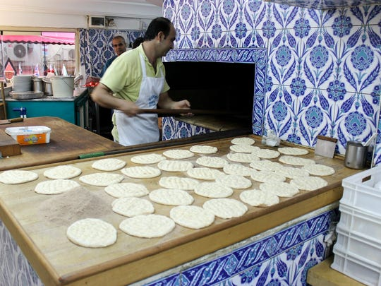 A baker tends the oven in a tiny restaurant on the