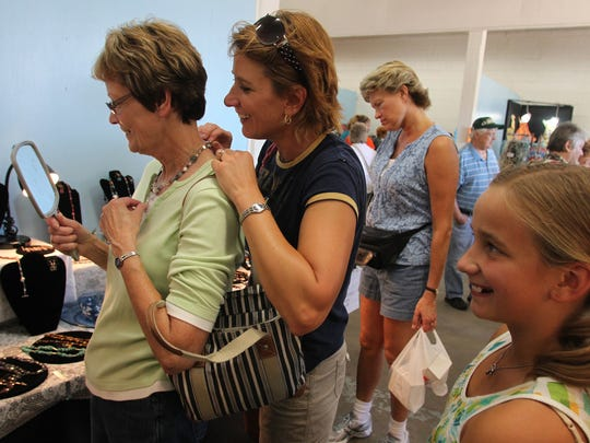 Bev Weinheimer of Juneau, left, looks in a mirror as she tries on a necklace along with her daughter Paula Norman of Tomahawk at Marathon Park during the Art in the Park part of Artrageous Weekend in Wausau in 2011.