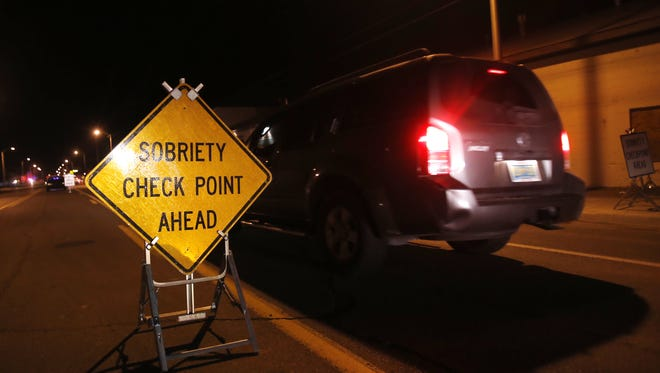 Vehicles slow down as they approach a sobriety check point on Dec. 19, 2014, on East Main Street in Farmington.