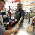 Timbo Hamilton, left, cashes in a winning scratch-off ticket with J.R. Hamilton at Eagles Express in Knightdale.