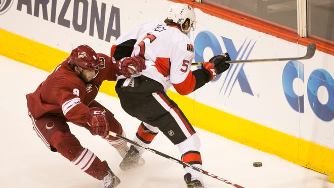 Coyotes center Tobias Rieder (left) and Senators defenseman Cody Ceci go after a loose puck during the first period of the NHL game at Gila River Arena in Glendale on Saturday, January 10, 2015.
