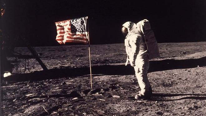 "In this July 20, 1969, file photo, astronaut Edwin E. ""Buzz"" Aldrin Jr. stands next to a U.S. flag planted on the moon during the Apollo 11 mission. Aldrin and Neil Armstrong were the first men to walk on the lunar surface."