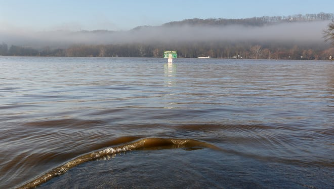 The parking lot of the Anderson Ferry on River Road is closed as the Ohio River flows over its banks Sunday morning. According to the National Weather Service, the Ohio River is expected to slowly fall over the next several days but will remain above flood stage until at least Wednesday.