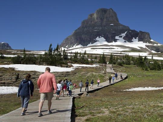 Visitors hike on the Hidden Lake Nature Trail at Logan Pass.