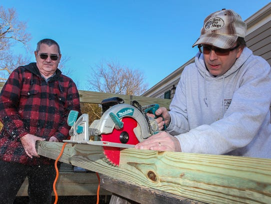 John Kline and Chris Palutis of Smyrna Home Depot work on building a deck for a disabled veteran.