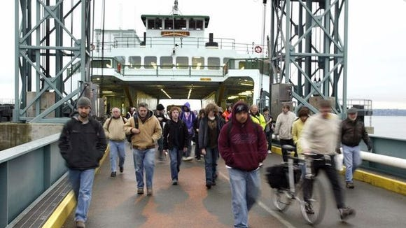 Commuters rush to depart from the ferry Klahowya at the Southworth ferry dock on Tuesday afternoon.