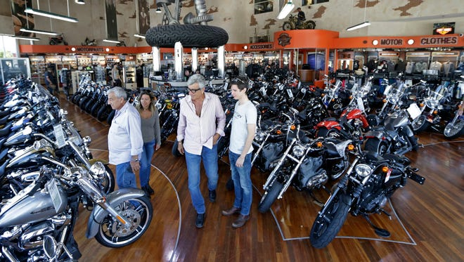 In this Tuesday, April 25, 2017, photo, customers look at Harley-Davidson motorcycles in the showroom at a dealership in Miami. On Tuesday, Aug. 15, 2017, the Commerce Department reports on business stockpiles in June. (AP Photo/Alan Diaz)