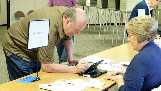 Voters sign in at White Oak Christian Church in Colerain Township.