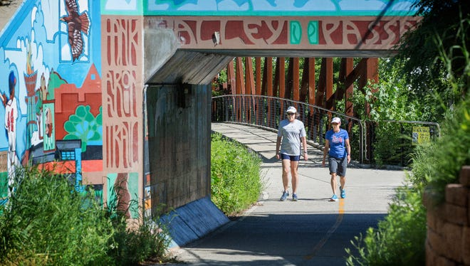 Nancy White (left) of Milwaukee and Mary Joy Hubbs of Muskego walk along the Hank Aaron State Trail near the Urban Ecology Center in the Menomonee Valley.