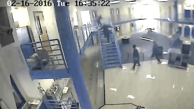 This screen shot of a Washoe County Jail surveillance video shows Deputy Michel Eubanks rushing up the stairs as an inmate with a sheet tied around his neck prepares to jump over the railing. Eubanks and two other inmates saved the man's life.