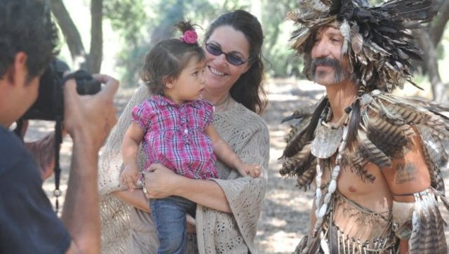 Michael Robinson Chavez, left, takes a photo of his daughter Olivia Robinson, 14 months, and his wife, Alexandra Abella, with Chumash Indian David Paul Dominguez at the Chumash Indian Museum in Thousand Oaks in 2011.