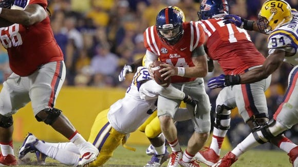 Ole Miss quarterback Bo Wallace is brought down by an LSU defender.