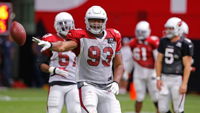 Arizona Cardinals defensive end Calais Campbell (93) flips the ball to an official after an interception during training camp Tuesday, August 4, 2015, in Glendale.